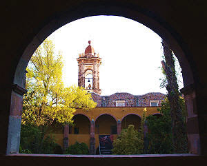 One of the towers of Las Monjas church in San Miguel de Allende, seen through the arches of Bellas Artes art school